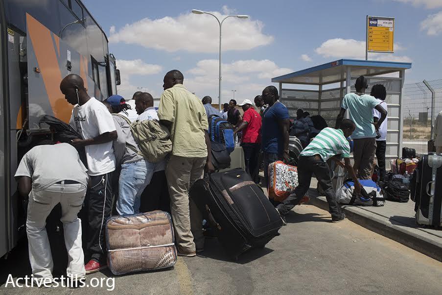 Dozens of asylum seekers crowd around a bus after being released from Holot detention center. According to Interior Minister Silvan Shalom, the asylum seekers are forbidden from living or working in Eilat and Tel Aviv, where large refugee communities live, August 25, 2015. (photo: Oren Ziv/Activestills.org)