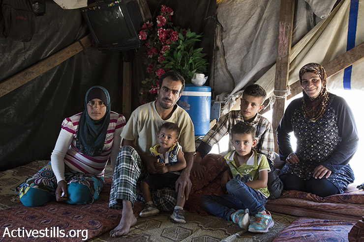 Nawaja family sits in the family's tent that is salted for demolition by Israeli authorities, Susya, West Bank, July 3, 2015. (photo: Keren Manor / Activesitlls.org)