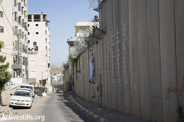 A Palestinian man climbs over the Israeli Wall from the West Bank town of al-Ram to the East Jerusalem neighbourhood of Beit Hanina, to attend the Friday prayer in Al-Aqsa Mosque, in the town of Al-Ram, near the Qalandiya checkpoint between the West Bank city of Ramallah and Jerusalem, on the second Friday of the Muslim holy month of Ramadan, July 3, 2015. (Oren Ziv / Activestills.org)