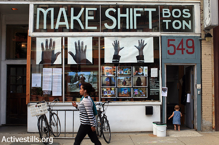 'Obliterated Families in Gaza' photo street-exhibition hangs in a window-shop in Boston, MA, July 14, 2015. The street-exhibition mark a year to the 2014 Israeli military offensive on the Gaza Strip featuring photos of families killed during the attacks. (Tess Schaflan / Activestills.org)