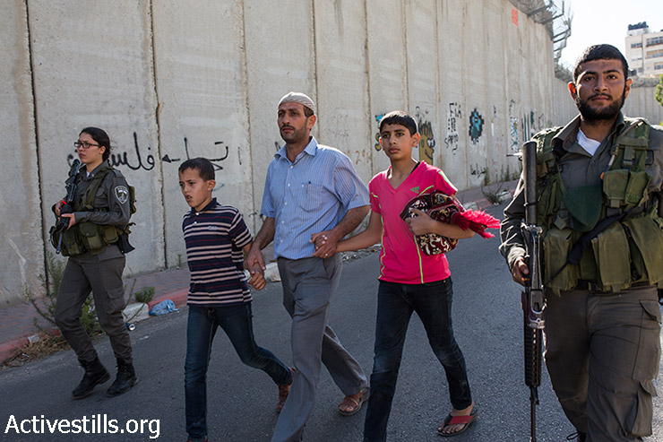 Israeli policemen arrest Palestinians after they climb over the Israeli Wall to attend the Friday prayer in Al-Aqsa Mosque, in the town of Al-Ram, near the Qalandiya checkpoint between the West Bank city of Ramallah and Jerusalem, on the second Friday of the Muslim holy month of Ramadan, July 3, 2015. (photo: Yotam Ronen / Activestills.org)