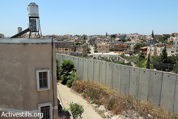The Israeli wall separates families of the West Bank village of Nazlet Issa (Right) and Baqa Al-Gharbiya town, inside the green line (Left), July 17, 2015. (photo: Ahmad al-Bazz / Activestills.org)