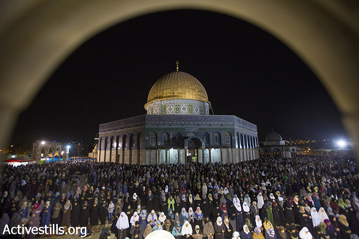 Palestinian Muslim worshippers pray overnight during Laylat al-Qadr, outside the Dome of the Rock in the Al-Aqsa mosque compound in Jerusalem's Old City, July 13, 2015. Layal al-Qadr, Night of Destiny, falls on the 27th day of the fasting month of Ramadan, marking the night Muslims believe the first verses of the Koran were revealed to the Prophet Mohammed through the archangel Gabriel. (photo: Fiaz Abu-Rmeleh / Activestills.org)