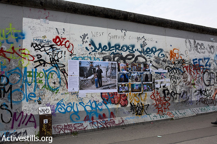 'Obliterated Families in Gaza' photo street-exhibition hangs on the East Side Gallery, on the remains of the Berlin Wall, Berlin, Germany, July 12, 2015. The street-exhibition mark a year to the 2014 Israeli military offensive on the Gaza Strip featuring photos of families killed during the attacks. The exhibition was put by activists in various locations in the city. (photo: Anne Paq / Activestills.org)