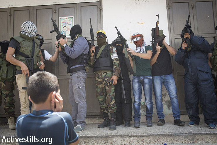 Armed and masked Palestinian militants raise their weapons during the funeral of Mohammad Abu Latifa in the Qalandiya refugee camp near the West Bank city of Ramallah on July 27, 2015. Abu Latifa was shot and killed as he was running away across a roof to avoid his arrest during an army raid. (photo: Oren Ziv / Activestills.org)