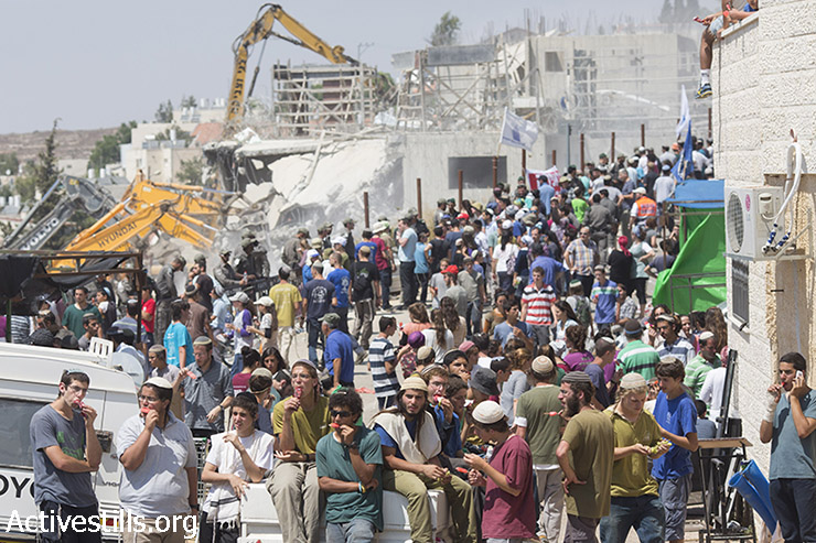 Israeli police forces stand guard while Israeli settlers watch on as bulldozers, under an Israeli High Court ruling, start the demolition of the so-called Dreinoff buildings in the settlement of Beit El, north of Ramallah in the occupied West Bank, 29 July, 2015. (photo: Oren Ziv / Activestills.org)