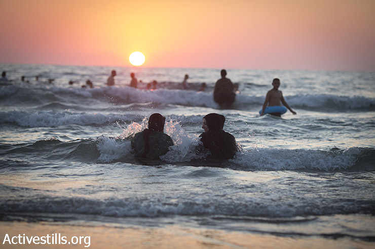 Palestinian women enjoy the Mediterranean Sea during the second day of the Eid al-Fitr holiday as the sun sets in Jaffa, July 18, 2015. Israeli authorities issued thousands of permits for Palestinians living in the West Bank, allowing them to visit Israel during the three-day holiday that marks the end of the holy fasting month of Ramadan. (photo: Oren Ziv / Activestills.org)