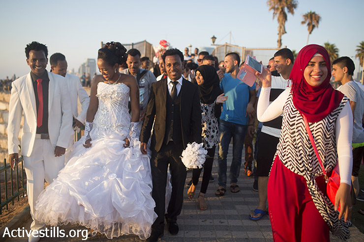 A Palestinian youth takes photos with her cellphone of Eritrean African asylum seekers on their wedding day in the Mediterranean Sea during the second day of the Eid al-Fitr holiday as the sun sets in Jaffa, July 18, 2015. (photo: Oren Ziv / Activestills.org)