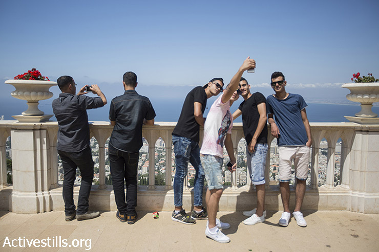 Palestinians, many of whom came from the West Bank, are seen in Haifa during the last day of the Eid al-Fitr, July 19, 2015. Israeli authorities issued thousands of permits for Palestinians living in the West Bank, allowing them to visit Israel during the three-day holiday that marks the end of the holy fasting month of Ramadan. (photo: Fiaz Abu-Rmeleh / Activestills.org)