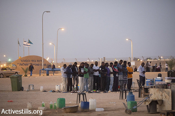 African asylum seekers jailed in Holot detention center pray after eating an Iftar meal, a traditional meal to break the day's fasting during the holy Muslim month of Ramadan, Negev Desert, July 5, 2015. (photo: Oren Ziv / Activestills.org)