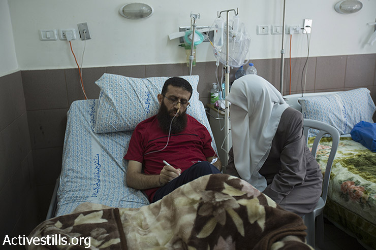 Palestinian Khader Adnan, who staged a 56-day hunger strike against his administrative detention in Israeli prison, lies in Makassed hospital near his wife, East Jerusalem, July 16, 2015. Adnan, 37, was released before dawn on July 12, 2015 and is receiving treatment for the medical consequences of his hunger strike. (photo: Ahmad al-Bazz / Activestills.org)
