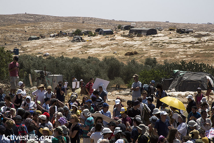 Palestinian, Israeli and international activists march next to the village of Susiya to protest its imminent demolition and the forced transfer of its residents, South Hebron Hills, West Bank, July 24, 2015. The activists marched through the village, stopping at various homes along their way to hear the stories of families facing eviction and transfer. At the end of the demonstration activists hung a massive banner in view of passing settlers, declaring that Susiya is here to stay. (photo: Keren Manor / Activestills.org)