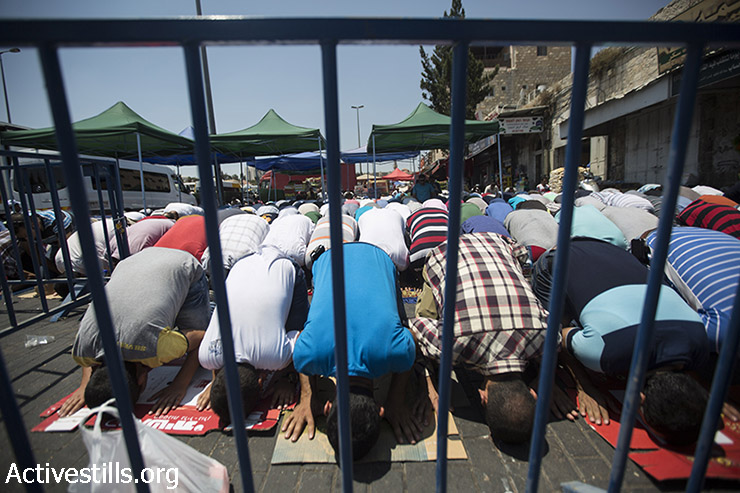 Guarded by Israeli policemen, Muslim worshipers pray on the streets outside Jerusalem's old city, July 31, 2015, following restrictions by Israeli police to only allow men above 50-year-old to access the Al-Aqsa Mosque compound.  Israel limited the accesses to Al Aqsa follwing an arson attack by Jewish settlers in the village of duma, where 18-month-old Palestinian toddler Ali Saad Dawabsha died. (photo: Fiaz Abu-Rmeleh / Activestills.org)