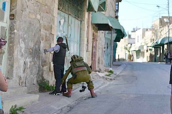 Soldier frisks Palestinian man in Hebron.
