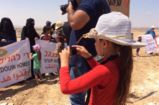 A Bedouin girl from Umm al-Hiran takes photos at a demonstration against the destruction of the village, August 27, 2015. (photo: Michal Rotem)