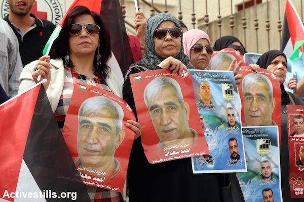 Palestinians protest in front of the ICRC building in Nablus holding photos of loved-ones being held in administrative detention by Israel. The demonstrators were demanding that the ICRC intervene to stop the practice, Nablus, West Bank. September 10, 2015. (Ahmad Al-Bazz/Activestills.org)
