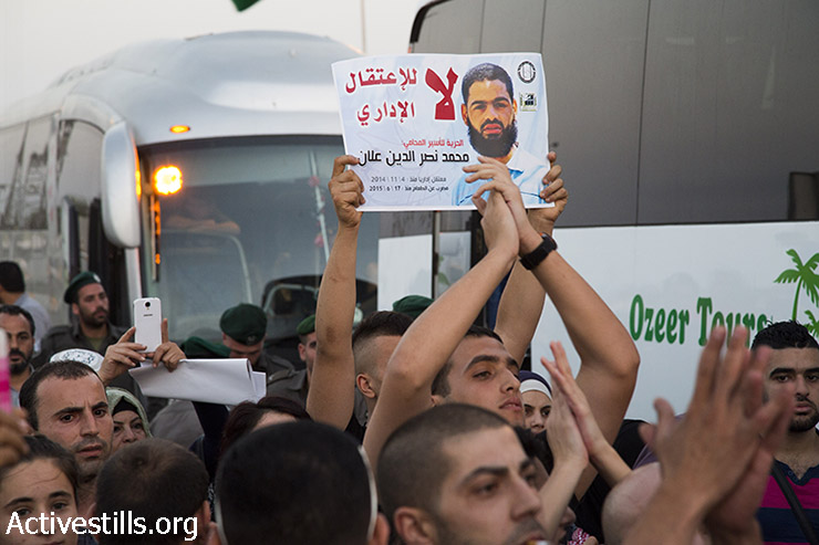 Palestinian activists hold up photos of administrative detainee, Muhammad Allan, during at the entrance to the Israeli city of Ashkelon, where Allan was being treated at Barzilay Hospital, August 17, 2015. (photo: Keren Manor/Activestills.org)