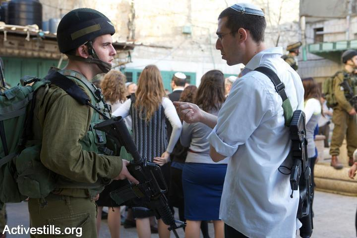 File photo of an Israeli soldier speaks with an armed Israeli settler in the Old City of Hebron. (Anne Paq/Activestills.org)