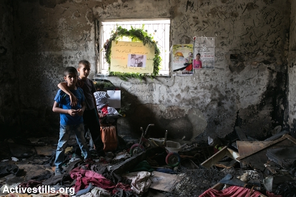 Children inside the burned Dawabsha family home before the funeral of Reham Dawabsha in the West Bank village of Duma, September 7, 2015. Reham was the third family member to die as a result of the July arson attack by suspected Jewish extremists. (Yotam Ronen/Activestills.org)