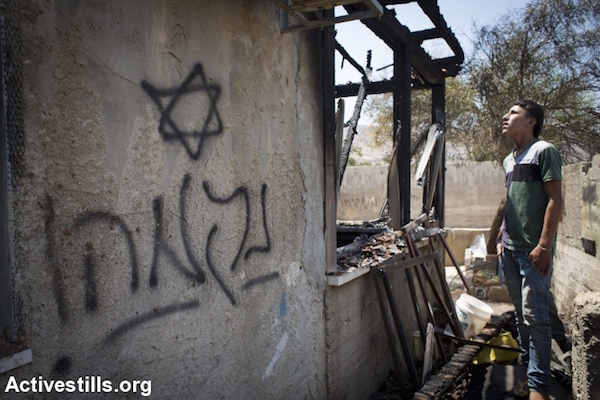 "A Palestinian youth looks at Hebrew-language graffiti reading ""revenge"" on the Dawabsha family home, which was set on fire by Israeli extremists killing three members of the family, July 31, 2015. (Oren Ziv/Activestills.org)"