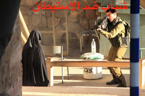 Hadeel al-Hashlamon stands frozen at the 'Shoter' checkpoint as soldiers train their weapons on her in downtown Hebron. (Photo courtesy of Youth Against Settlements)
