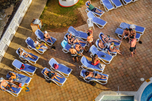 Illustrative photo of tourists sunbathing at a hotel pool. (Photo by Benoit Daoust/Shutterstock.com)