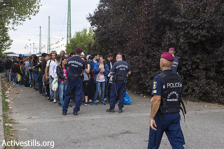 Hungarian police officers organize the refugees who arrived at the train station into rows of four as they prepare to march toward the Austrian border. (Mareike Lauken/Activestills.org)