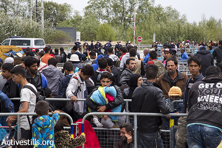 Refugees wait behind barricades and makeshift lanes at the Austrian border. (Keren Manor/Activestills.org)