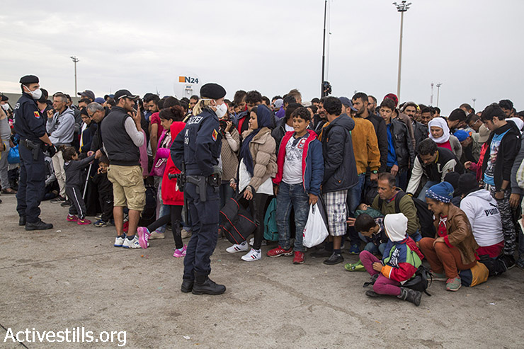 Refugees wait for buses at the transit camp. (Keren Manor/Activestills.org)
