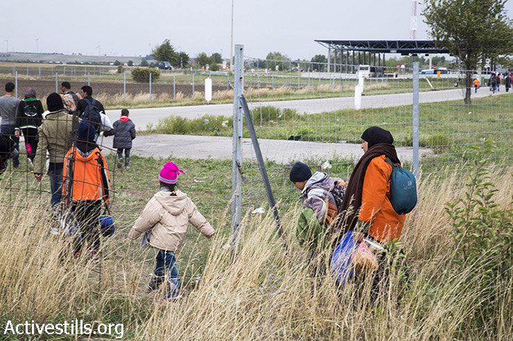 Refugees cross the border through a whole in the fence. (Keren Manor/Activestills.org)