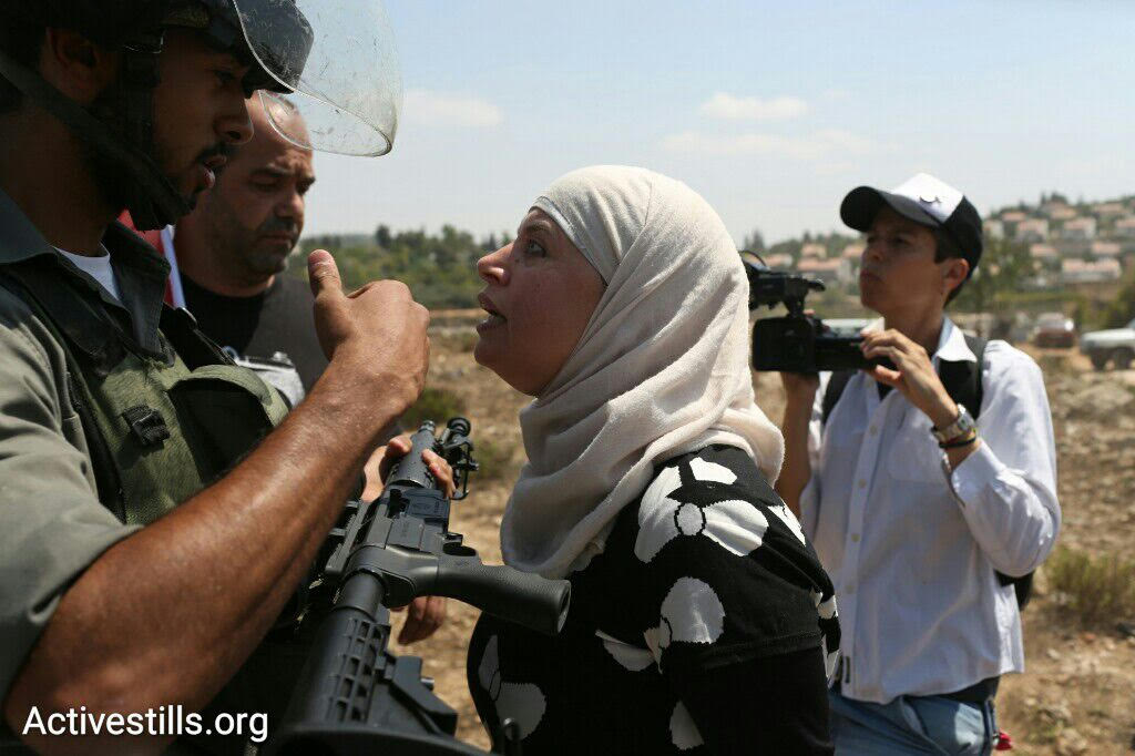 A Palestinian protester confronts Israeli Border Policemen during a protest against the occupation in the West Bank village of Nabi Saleh, September 4, 2015. (photo: Oren Ziv/Activestills.org)