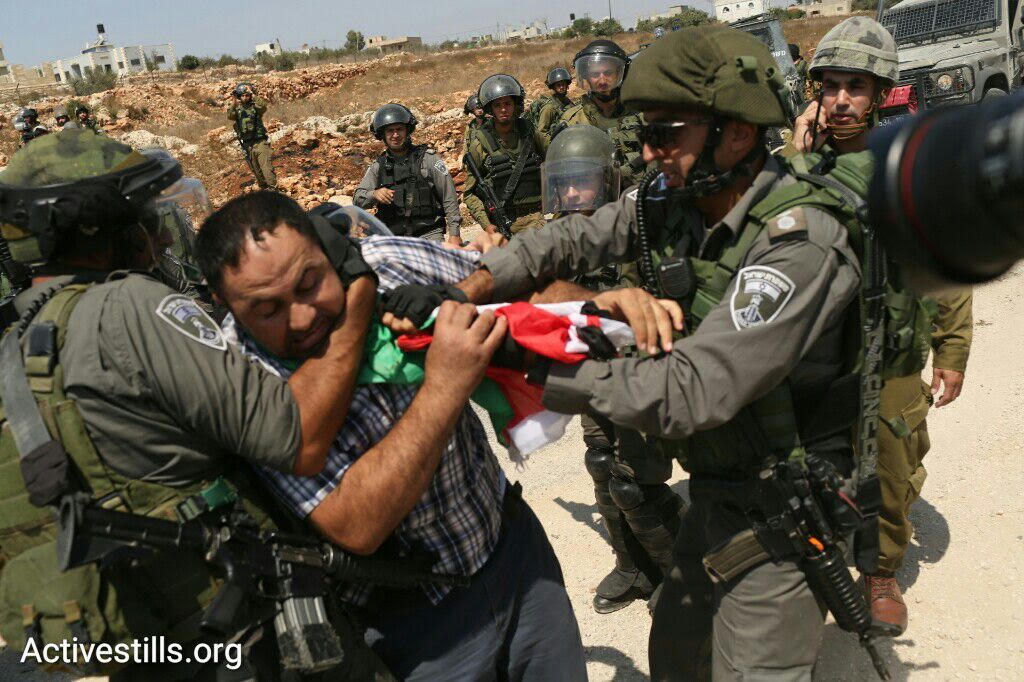 Israeli Border Policemen arrest a Palestinian protester during the weekly anti-occupation demonstration in the West Bank village of Nabi Saleh, September 4, 2015. (photo: Oren Ziv/Activestills.org)