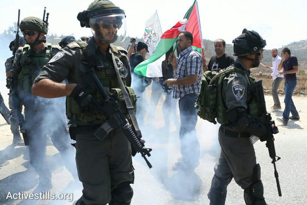 Israel Border Policemen throw stun grenades during an anti-occupation protest in the West Bank village of Nabi Saleh, September 4, 2015. (photo: Oren Ziv/Activestills.org)