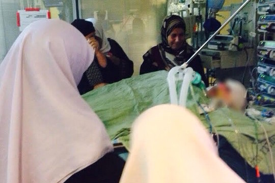 Women of the Dawabsha family sit around Reham's hospital bed, September 5, 2015. (Photo: Samah Salaime)