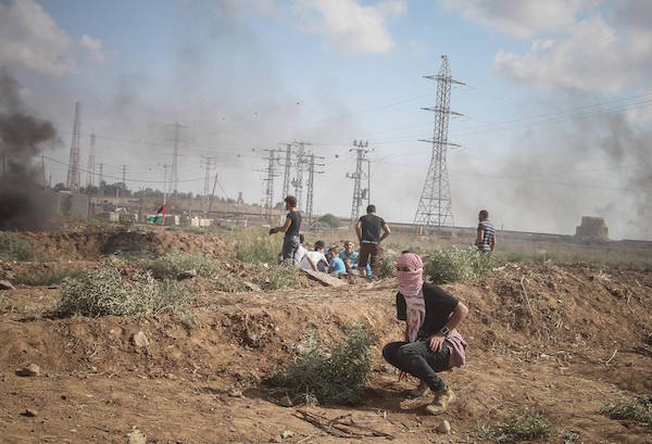 A Palestinian protester crouches during a demonstration in the Gaza Strip that left six Palestinians dead and over 130 wounded when IDF opened fire over the border, 9 October, 2015. (Ezz Za'noun)
