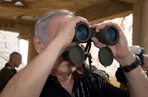 Prime Minister Benjamin Netanyahu looks through binoculars toward the Gaza Strip during a visit to an army base in southern Israel, October 20, 2015. (Haim Zach/GPO)