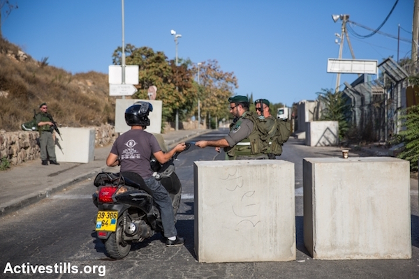 Israeli police stop and check a Palestinian man exiting the Jabel Mukaber neighborhood of East Jerusalem, October 15, 2015. Following a spate of over a dozen stabbing attacks carried out by Palestinian residents of East Jerusalem, Israel blocked off and erected checkpoints at the entrances and exits of most Palestinian neighborhoods of Jerusalem. (Yotam Ronen/Activestills.org)
