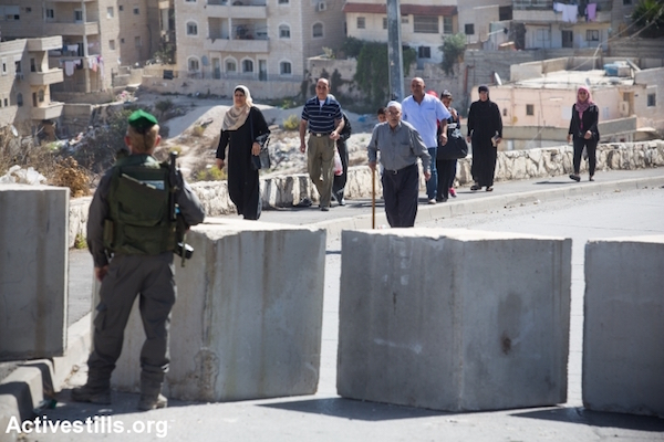 Israeli police stop and inspect Palestinian residents of Jerusalem as they enter and exit their neighborhood, Issawiya, East Jerusalem, October 15, 2015. Following a spate of over a dozen stabbing attacks carried out by Palestinian residents of East Jerusalem, Israel blocked off and erected checkpoints at the entrances and exits of most Palestinian neighborhoods of Jerusalem. (Yotam Ronen/Activestills.org)