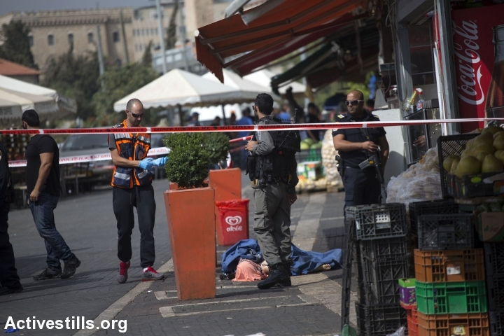 The body of a Palestinian teen is seen on the street near damascus gate, in Jerusalem, October 10, 2015. The teen, later identified as Ishaq Badran, 16, from Kafr Aqab, was shot and killed by the Israeli police after carrying out an alleged stabbing attack in the area. The death of the suspected attacker brings the total number of Palestinians killed since Oct. 1 to 10, while four Israelis, including two settlers, have been killed in the same time period. (photo: Anne Paq/Activestills.org)
