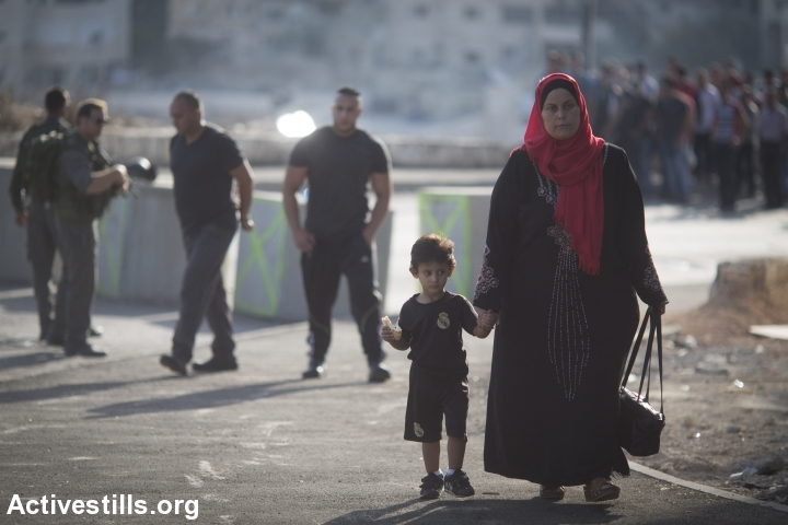 Israeli border policemen stop and check Palestinians going out of the East Jerusalem neighbourhood of Issawiya, on October 15, 2015. Israel set up checkpoints in the Palestinian neighbourhoods of east Jerusalem and mobilised hundreds of soldiers as a collective punishment after recent attacks by Palestinians. (photo: Oren Ziv/Activestills.org)