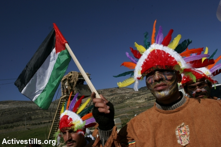 """Palestinian dress up as Native Americans during a protest as part of the campaign """"30 Days Against Roadblocks,"""" Huwwara Checkpoint outside of Nablus, January 14, 2007. Palestinian activists initiated the campaign to send a message to U.S. Foreign Minister Condoleezza Rice about daily life under occupation. (photo: Oren Ziv/Activestills.org)"""