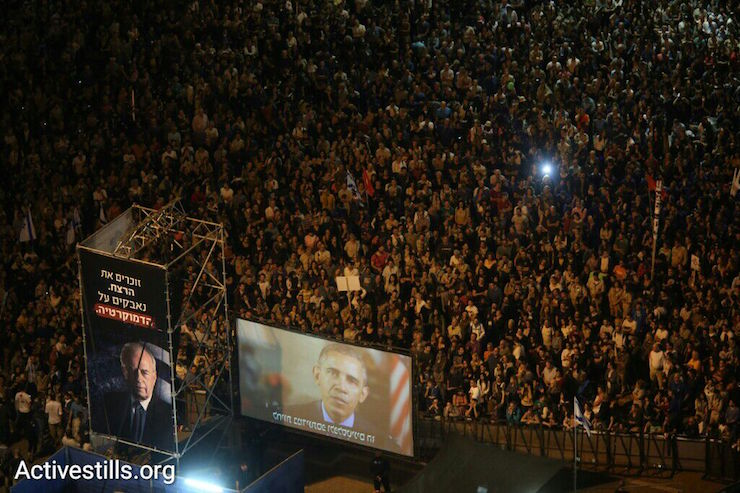 U.S. President Barack Obama delivers a video message to a Tel Aviv rally marking 20 years since the assassination of Israeli prime minister Yitzhak Rabin, October 31, 2015. (Oren Ziv/Activestills.org)