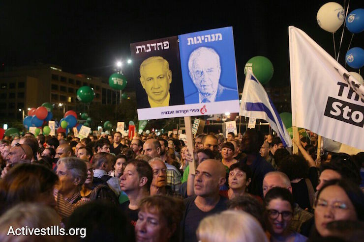 "A sign at the Rabin memorial rally featuring an image of Yitzhak Rabin (right) with the word ""leadership."" Above an image of Benjamin Netanyahu is the word ""cowardice,"" Rabin Square, Tel Aviv, October 31, 2015. (Oren Ziv/Activestills.org)"