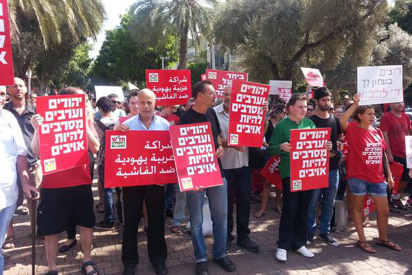 Members of Israeli communist party Hadash attend an anti-violence protest in Tel Aviv, October 9, 2015. (Photo by A. Daniel Roth) Most of the Hebrew signs read 'Jews and Arabs refuse to be enemies.'