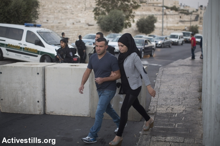 A Palestinian couple cross a roadblock set up by Israeli police in the Palestinian neighbourhood of Ras al-Amud in east Jerusalem, on October 14, 2015. Israel set up checkpoints in Palestinian neighbourhoods of east Jerusalem and mobilised hundreds of soldiers as a collective punishment after recent attacks by Palestinians. (photo: Oren Ziv/Activestills.org)