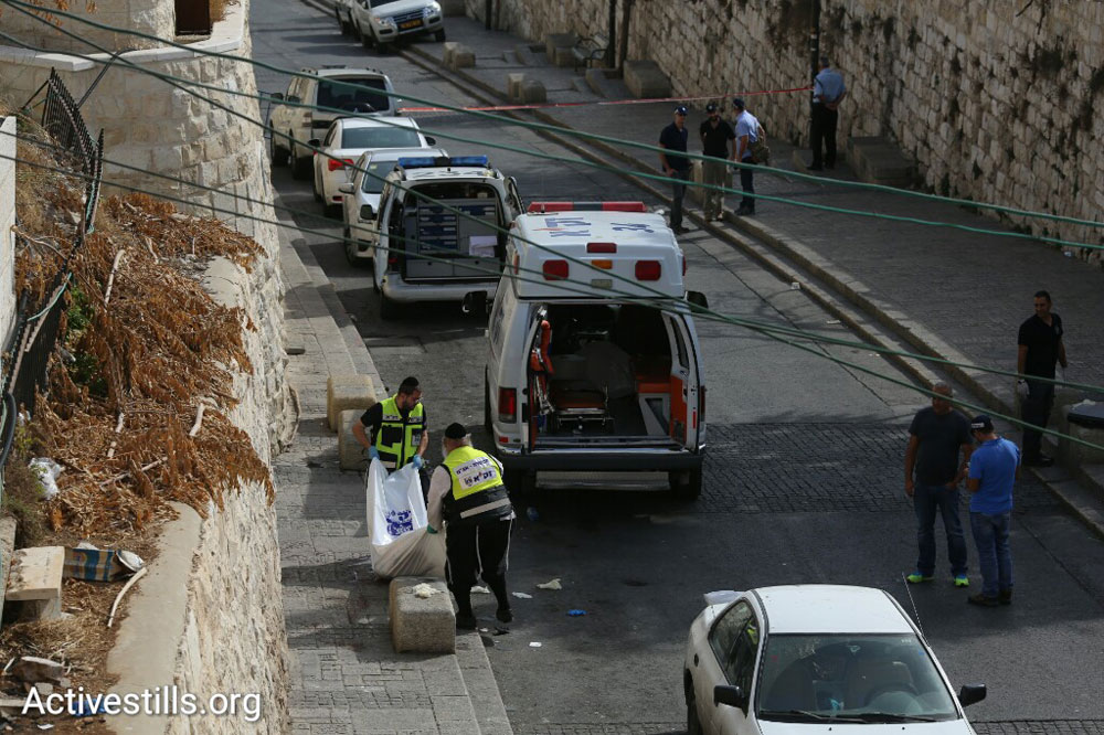First responders remove the body of a Palestinian man who carried out a stabbing attack in Jerusalem. Police shot him dead, October 12, 2015. (Oren Ziv/Activestills.org)