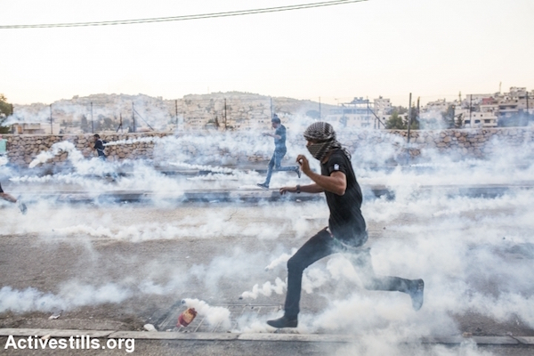 Palestinian protesters run from tear gas during clashes with Israeli forces near the Separation Wall in the West Bank city of Bethlehem, October 14, 2015. The protest took place after the funeral of Mutaz Ibrahim Zawahreh, 27, from Deheishe camp, who was shot dead by Israeli forces during clashes the day before. (Anne Paq/Activestills.org)