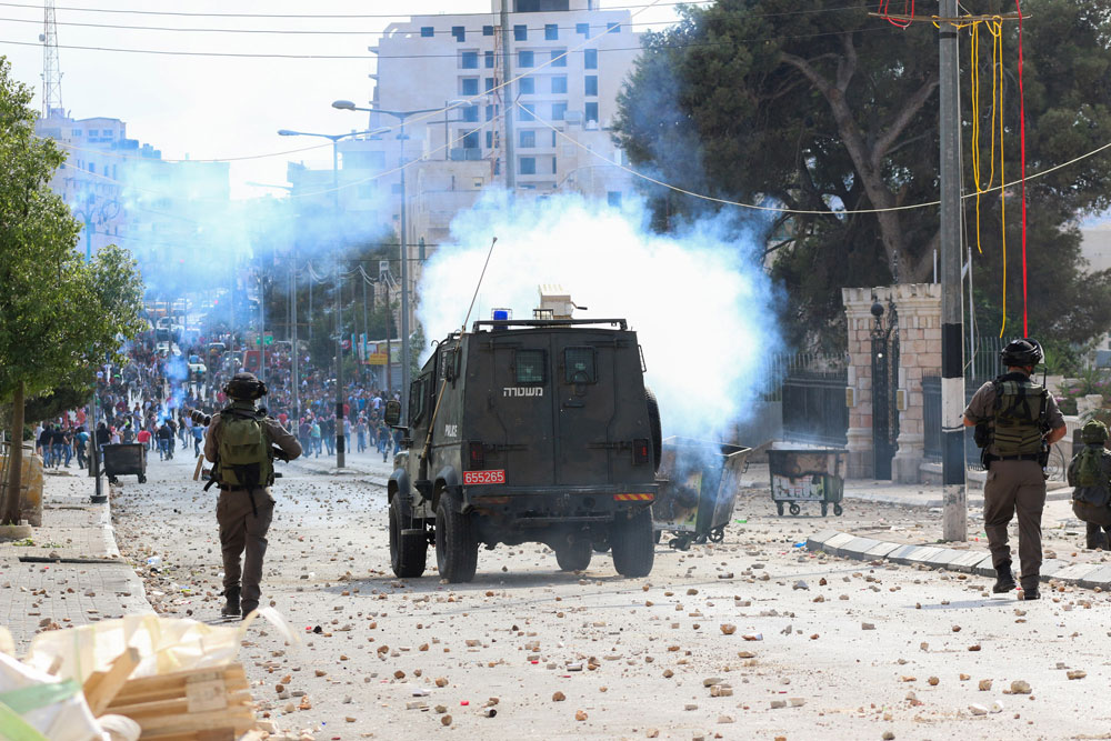 Palestinian youth clash with Israeli troops in Bethlehem following the funeral of a 13-year-old Palestinian boy who was killed by an IDF sniper during clashes, October 6, 2015. (Muhannad Saleem/Activestills.org)