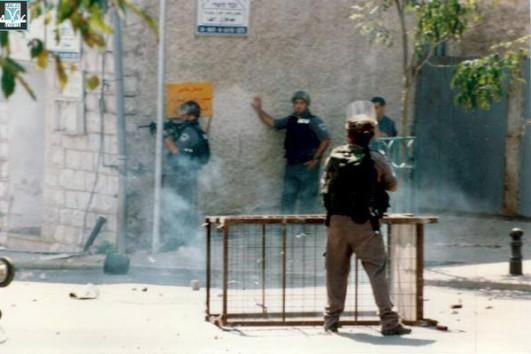 Israeli Border Police officers aim assault rifles toward Arab demonstrators in northern Israel during October 2000. (Courtesy of Adalah)