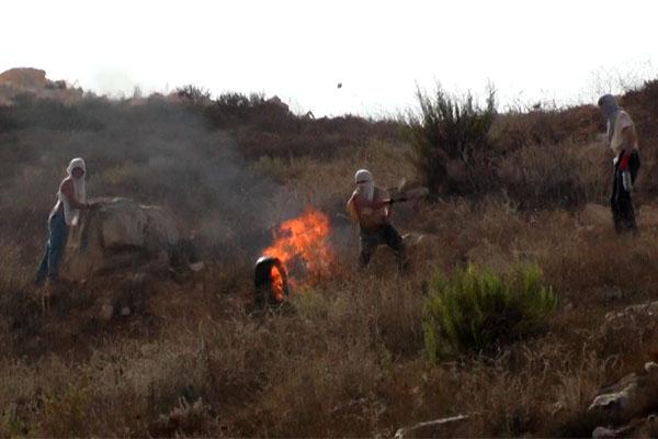 Screenshot of video showing Israeli settlers hurling burning tires at Palestinians in the West Bank village of Bur'in, October 3, 2015.